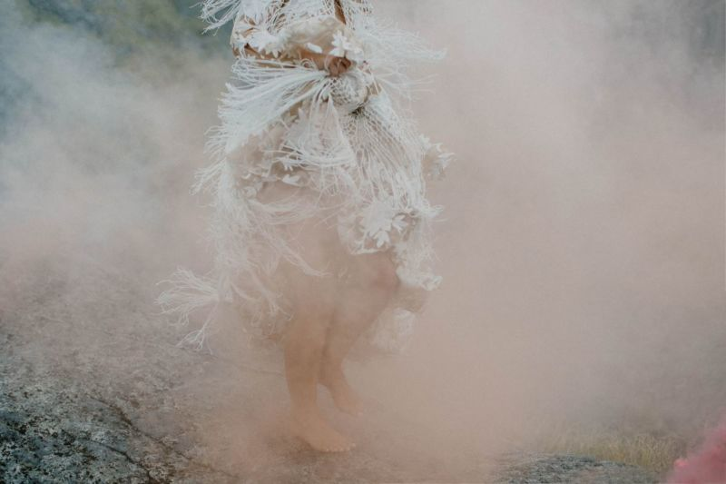 close up of bride swishing dress in cloud of smoke