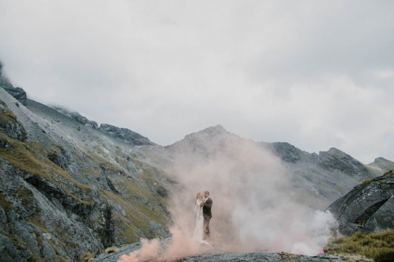 bride and groom in a cloud of pink smoke with mountains in the background