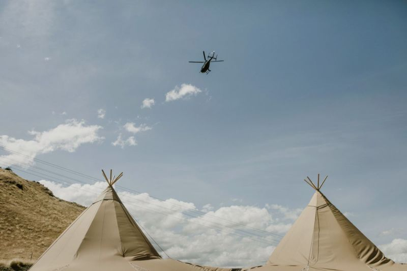 helicopter flying over tipis