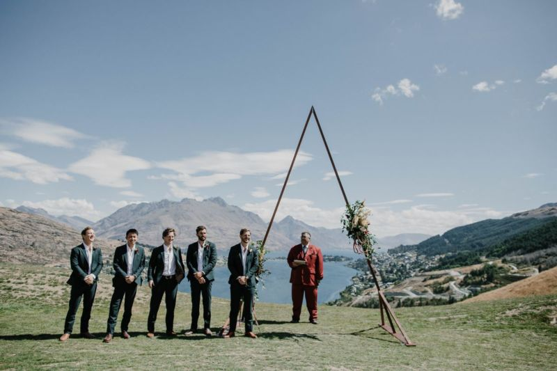 groom, groomsmen and celebrant waiting at the ceremony site with arch