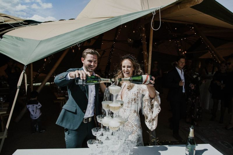 bride and groom happily filling champagne tower in tipi