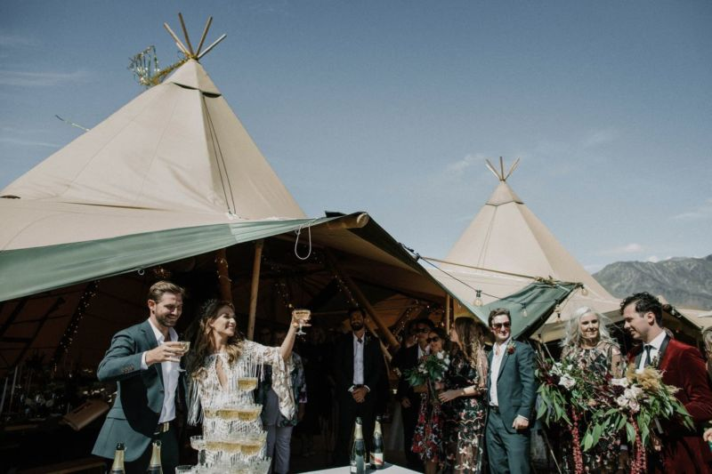 bride and groom cheers to the guests from the tipi with champagne glasses
