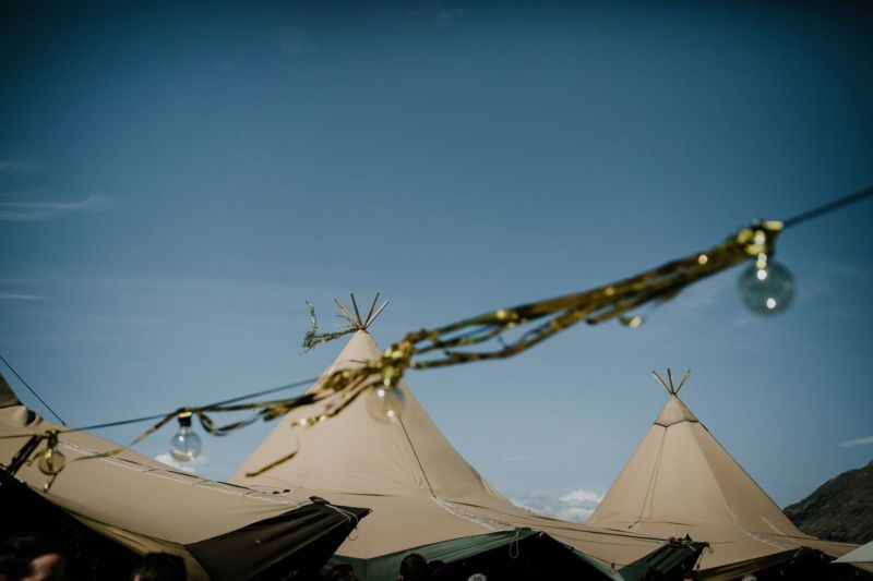 gold streamers stuck on festoon lights and tipi