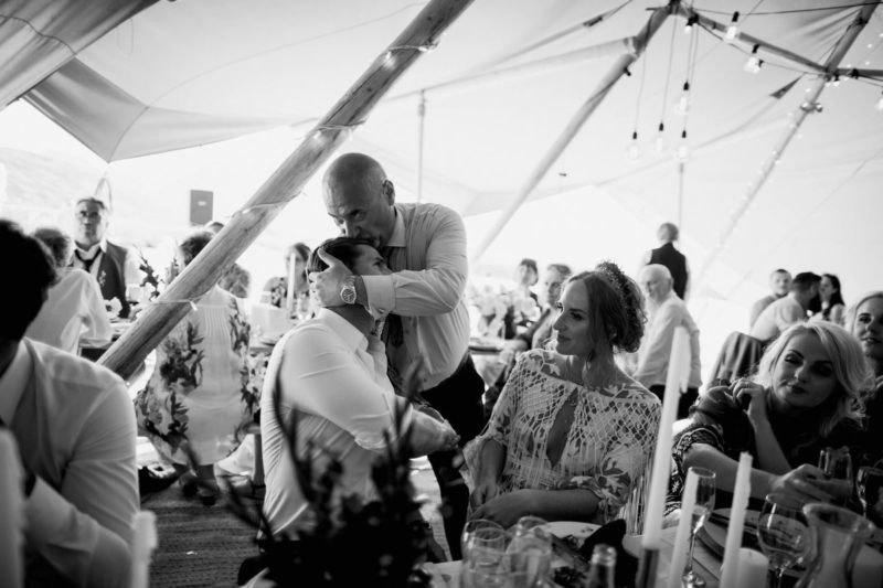 brides dad kissing groom on the head