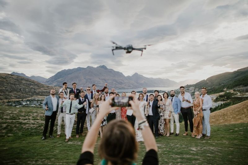 group photo with drone and guest with phone getting in the way