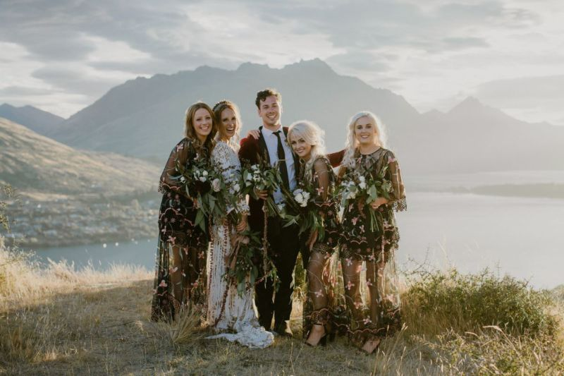 Bride, bridesmaid and bridesman pose for a portrait in sunset light in front of mountains and lake