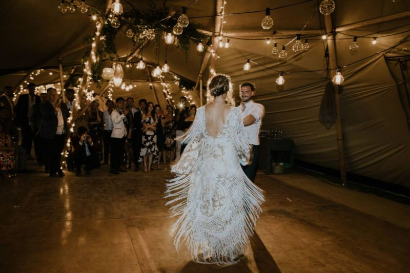 bride swinging dress on tipi dancefloor with back light