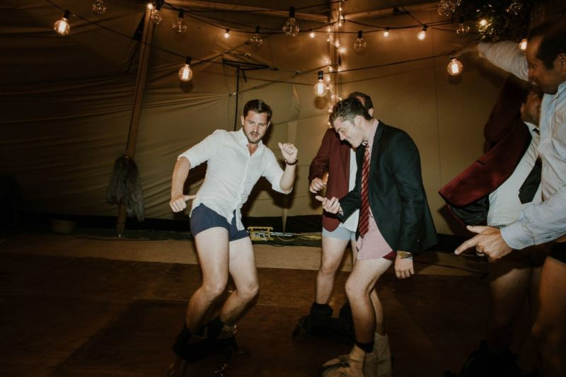 groom and men on dancefloor with pants down