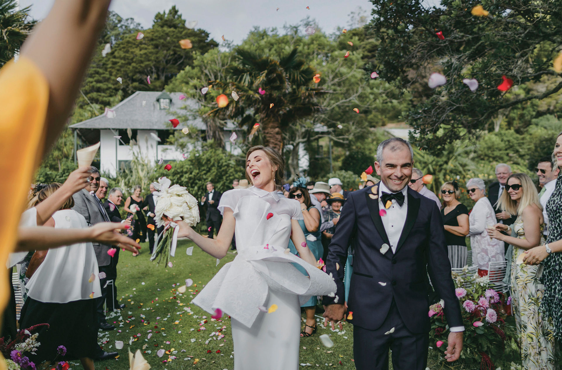 bride and groom just married walking down aisle surprised by confetti