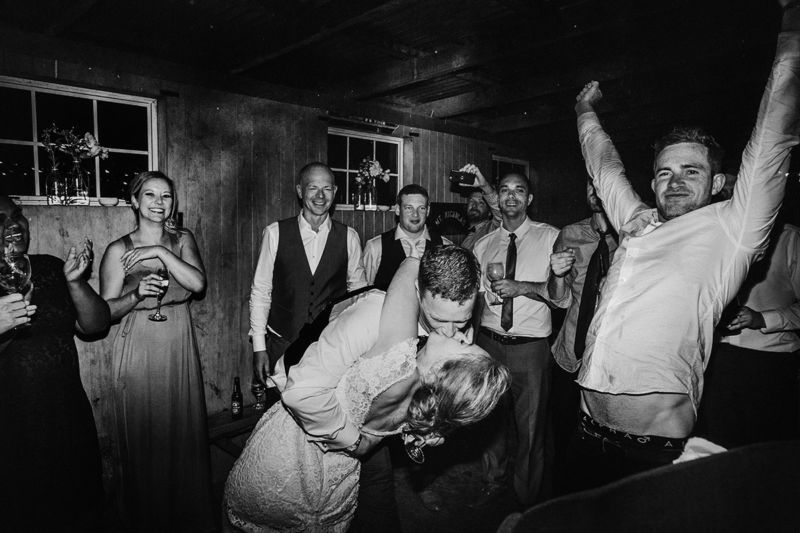 messy dance floor bride and groom kissing and guests celebrating