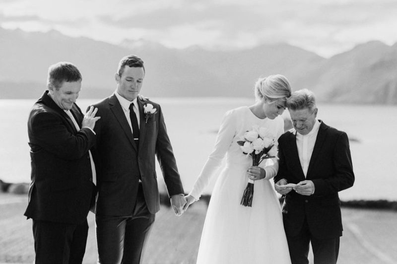 touching ceremony moment between bride and groom and their dads in wanaka