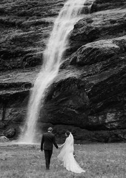 Bride and groom in front of a waterfall in NZ