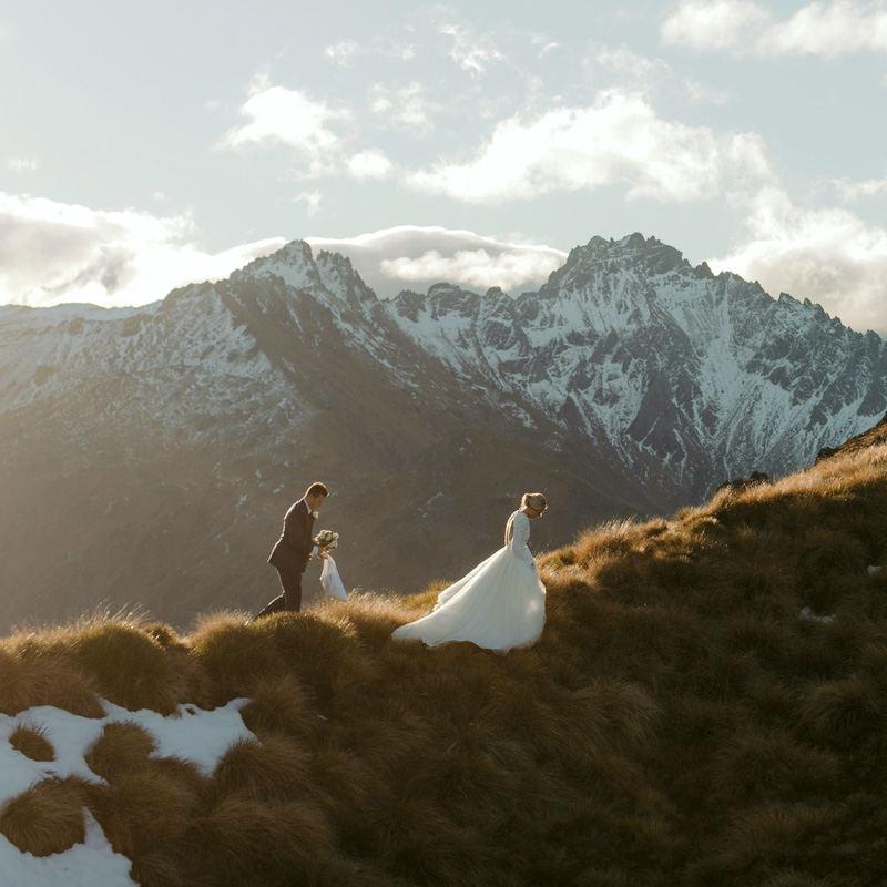 bride and groom on mountaintop walking on ridge